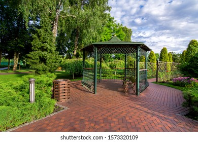 an iron gazebo with a bench and paving stone tiles in the garden with a lawn and evergreen thuja near the canopy of the urn and in the bushes an iron lantern on a sunny day with a cloudy sky, nobody.