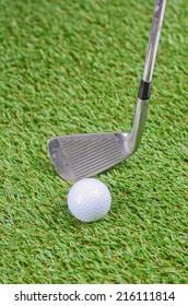 Iron and golf ball on green grass field