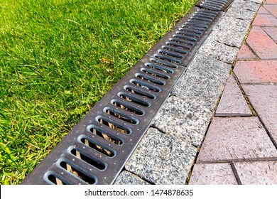iron grate of a drainage system for storm water drainage from a pedestrian sidewalk near a green lawn.