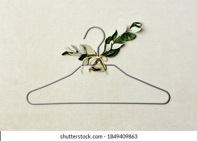 Iron hanger with sprig of the tree with leaves on linen background. Natural aestetic, Eco-friendly, Chic, Cozy, Sustainable Sale concept. Zero waste Black friday. Space for text.