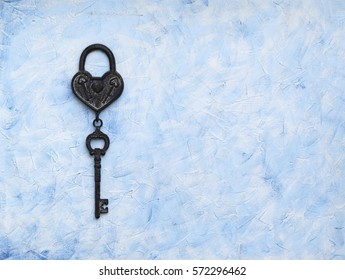 iron key from the lock lying on a wooden vintage background, top view