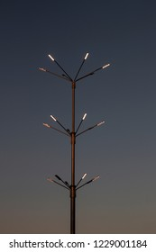 iron lamppost with the lights on against the dark evening sky