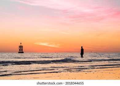 An Iron Man and a tide marker silhouetted at sunset in April 2021.  This sculpture is part of Another Place, the art installation on Crosby beach near Liverpool.
