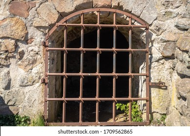 Iron metal rusty grating or prison bar on the window. The basement openings are closed with a special thick metal grating. Old ancient ruined stone castle. Walls of a medieval castle.