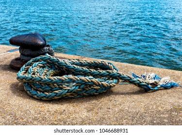 Iron mooring bollard with rope hawser on quay
