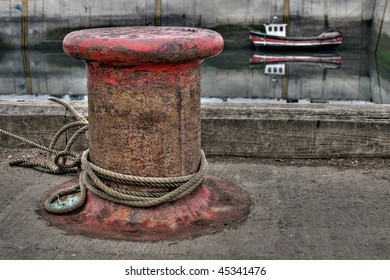 Iron mooring post on harbour wall
