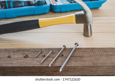 iron nail on a wooden table, Using hammer and nail on wood  background.