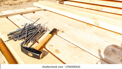 Iron nails and a hammer on a wooden background. Long, metal, carpenter's nails and a mallet lie on a bar for construction. Side view. space for text