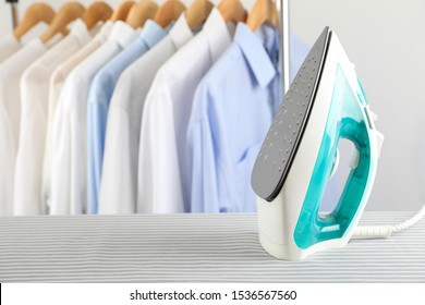 Iron on ironing board against light background, space for text
