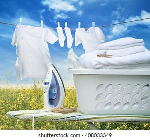 Iron on ironing board with laundry basket