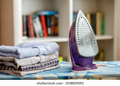 Iron on the ironing board next to a stack of ironed shirts - Shutterstock ID 1938059092