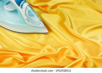 iron is on yellow satin fabric. delicate ironing concept
