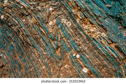 Iron ore texture closeup - natural minerals in the mine. Stone texture of open pit. Extraction of minerals for heavy industry - the texture of the rock containing iron ore and copper.
