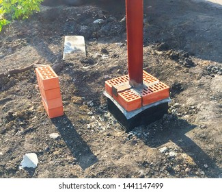 Iron pillar in the ground and red bricks. Start of construction of a fence in the park.
