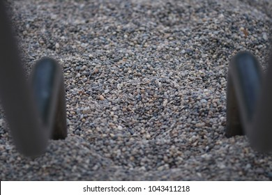 Iron pipes on a playground end up on pebbles. stones and metal construction underground with round pipes