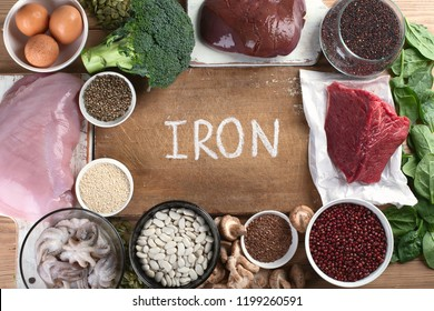 Iron rich foods as liver, beef, eggs,  lentil, bean,  broccoli, mushrooms, guinoa and seafood on wooden table. Healthy eating concept
