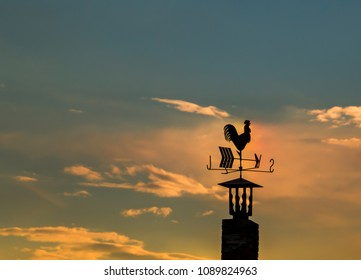 Iron rooster weather-vane showing a wind direction. Traditional weathercock on sunset heaven background.