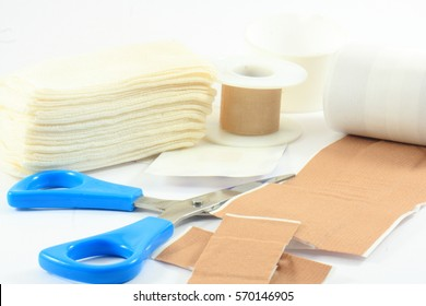 The iron scissors, bandages and plasters on a white background
