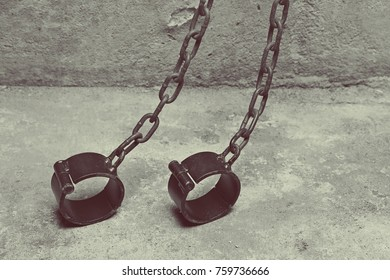 Iron shackles on a concrete background