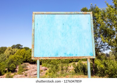 Iron sign in summer with copyspace. Billboard in blue of a blue color against the sky and trees. Space for your text.