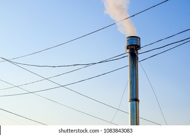 iron smokestack with icicles against the sky and wires