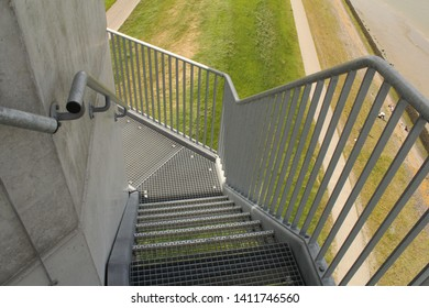 an iron stair with fence closeup at a tower and a green grass in the background