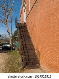 an iron staircase on the side of a red brick building