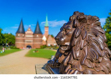 The iron statue of a lion in front of the medieval Holsten Gate (German: Holstentor) in Luebeck (German: Lübeck), Germany. The statue was designed by Harry Maasz in 1823.