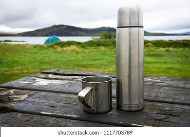 Iron Thermos and Mug On Campsite Background. Tingvadlavatn Lake, Iceland
