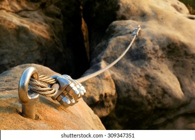 Iron twisted rope stretched between rocks in climbers patch.  Rope fixed in block by screws snap hooks. Detail of rope end anchored into sandstone rock