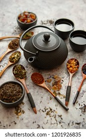 Iron vintage teapot and cups. Dried various kinds of tea on wooden spoons. Stone background with copy space