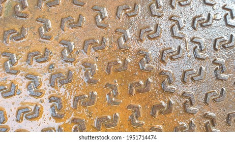 The iron is wet, the manhole cover is wet after the rain. The geometric pattern on a rusted metal plate. The pattern on a Manhole cover.