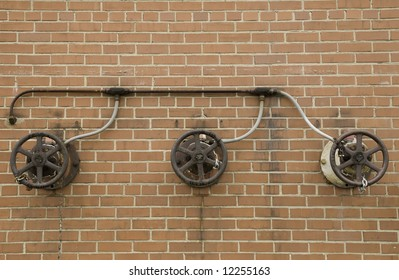 Iron wheels of three locked water valves connected to the same pipe on exterior red brick wall