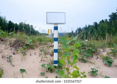 iron white with blue edge blank rectangular sign on white-blue iron base on nature sand  sky and trees background. mockup