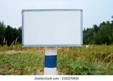 iron white with blue edge blank rectangular sign on white-blue iron base close up on nature sky and trees background. mockup