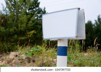 iron white with blue edge blank rectangular sign on white-blue iron base close up on nature sand  sky and trees background. mockup