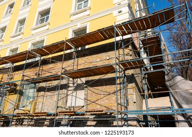 Iron and wooden scaffolding near the yellow house during reconstruction, building renovation during daytime. building exterior, construction and repair industry, yellow wall and windows