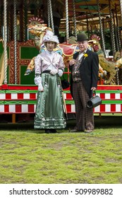 IRONBRIDGE, ENGLAND - JULY 21 2012 : Man and woman dressed in Victorian costume at the fairground carousel Blists Hill Working Museum, a popular tourist attraction. Ironbriidge, Shropshire, England.
