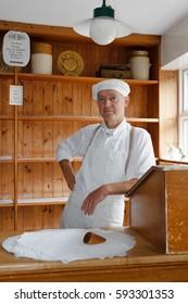 IRONBRIDGE, UK - CIRCA 2013: Baker at the Victorian Bakery shop store in Blists Hill Museum, Ironbridge, Shropshire, UK