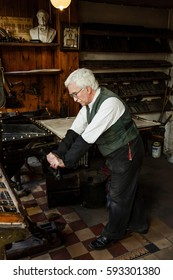 IRONBRIDGE, UK - CIRCA 2013: A man in period costume works a traditional printing press at Blists Hill Victorian Museum, Shropshire, UK