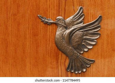 Irone Dove holds a palm branch, a metallic bas-relief which personifies international day of peace. Silhouette of pigeon dove holding olive branch on the wooden background