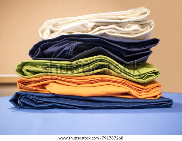 Ironed pile or stack of colorful fitted sheets, freshly washed, folded and stacked by professional ironers, on top of professional iron board