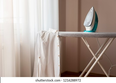 Ironed shirt hanging from an ironing board next to a hot iron. Selective focus on the iron