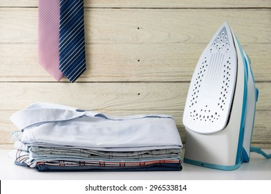 Ironing clothes laundry housework with stack of shirts and tie hanging