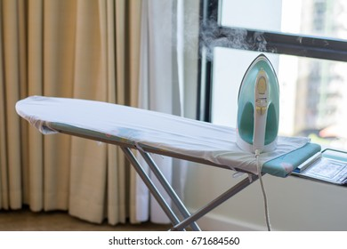 Ironing clothes on ironing board and laundry items.