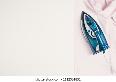 Ironing clothes top view isolated on white background. Ironing shirt seen from above during housework. Violet or pink iron isolated on white table.