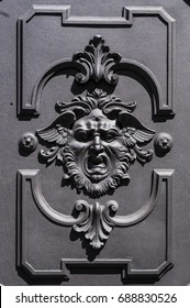 Ironwork, a door decorated with the engraving of an apotropaic mask