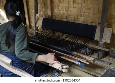 irrecognizable person is weaving using traditional wooden weaving tool sitting on bamboo floor at a bamboo traditional house.