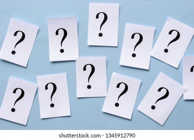 Irregular rows of printed question marks on white cards or signs arranged in a flat lay still life on a blue background in a conceptual image
