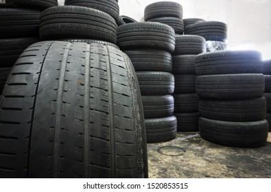 Irregular Tire Wear , Damaged black tire of side wear area on blurred pile old tyres background.